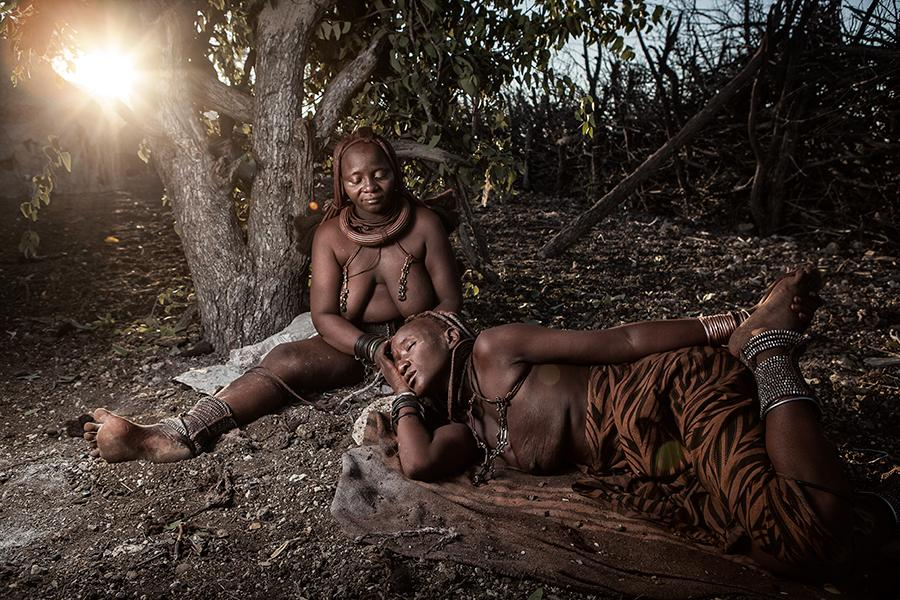 Himba woman applying tjize paste to another woman's hair. Photographed byBen McRae.