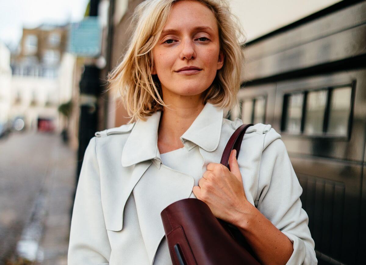 Jessica Kruger, founder of LUXTRA, wearing handbag, street in background