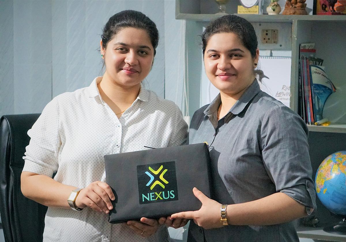 Nishita Baliarsingh and Nikita Baliarsingh holding the Nexus battery pack