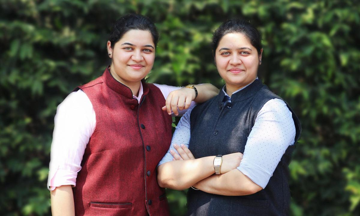 Nishita Baliarsingh and Nikita Baliarsingh, cofounders of Nexus Power, standing in front of greenery