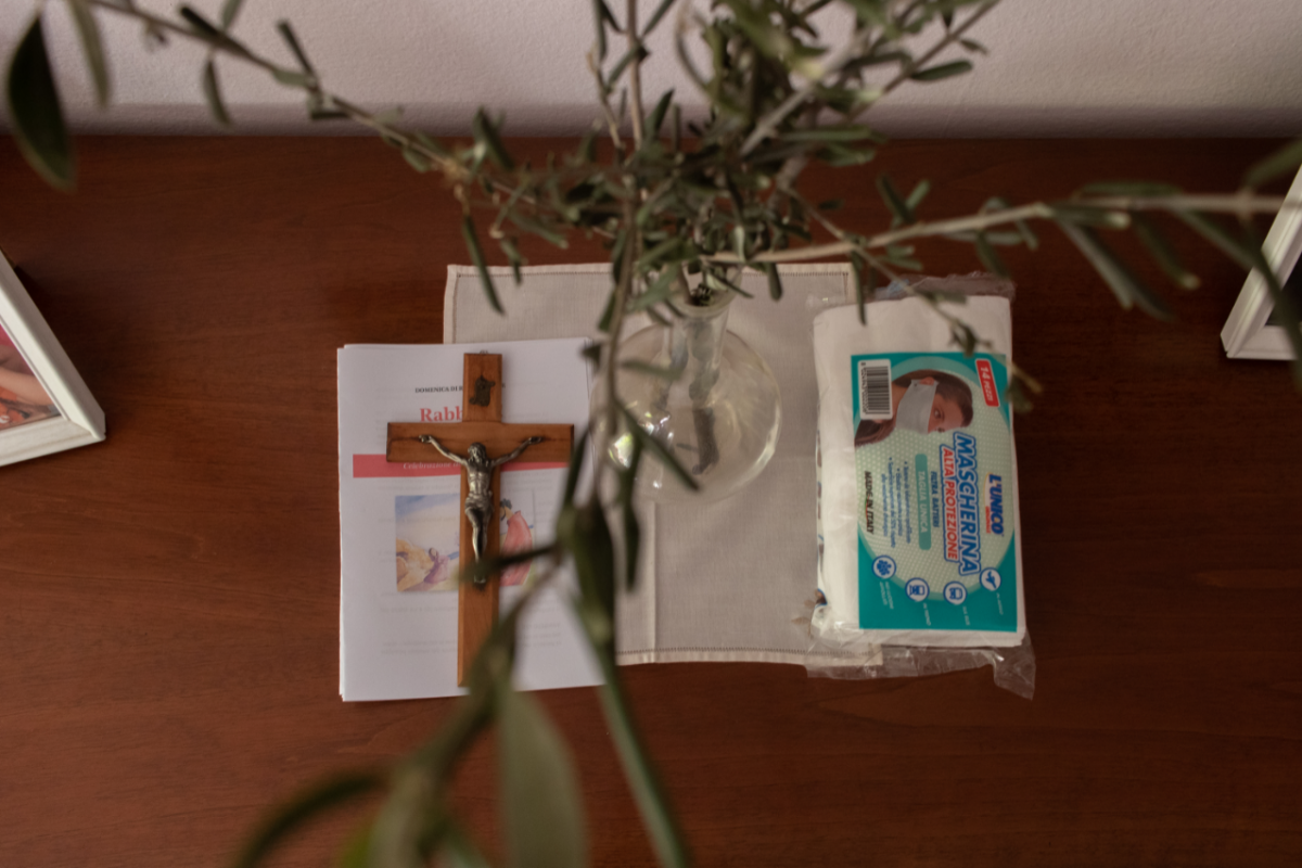 A table with rosemary in a vase, a prayer book, a small crucifix and face masks