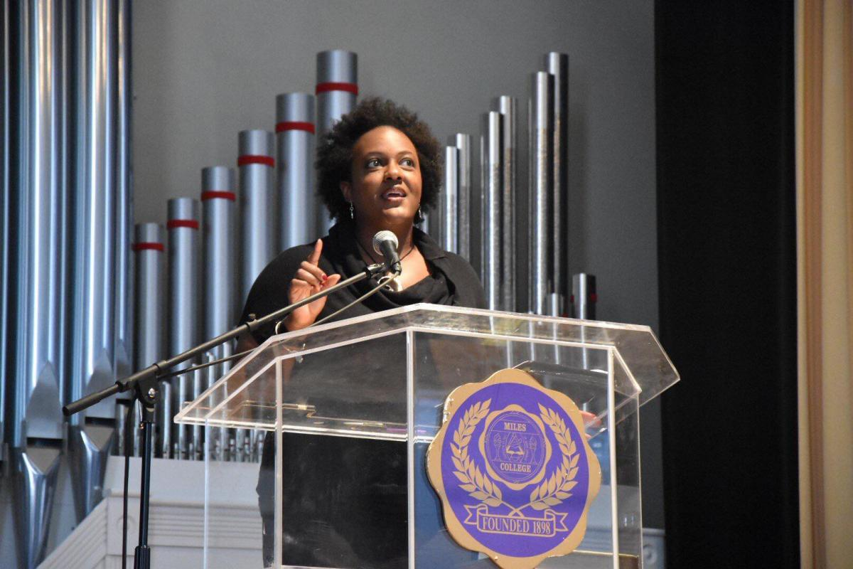 Heather McTeer Toney speaking on stage in front of a podium at Miles College.