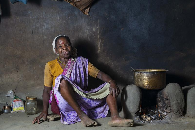 A woman sitting in her rustic kitchen. A towel is wrapped around her head to dry her wet hair.