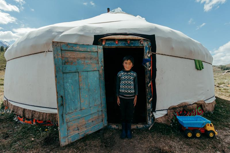 A boy in front of his yurt.
