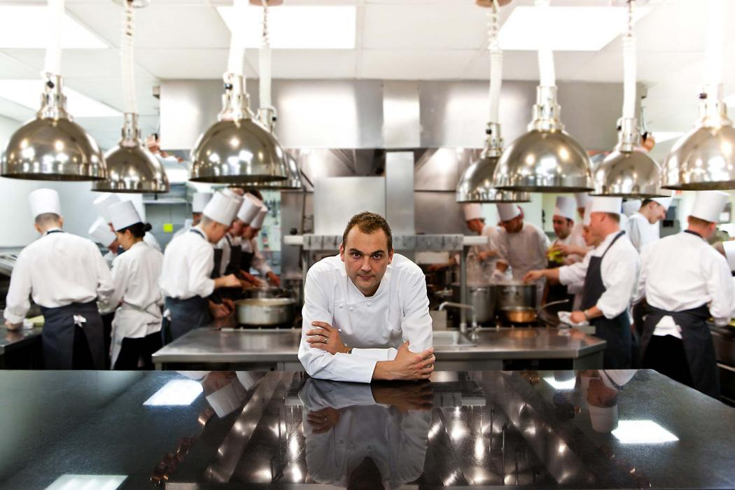 Executive head chef, Daniel Humm leaning on bench, looking at camera, in his kitchen at Eleven Madison Park Restaurant, NYC