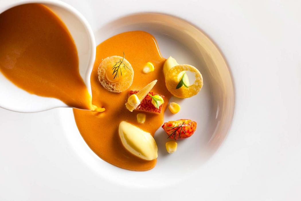 Creamy corn soup being poured into a white bowl at Eleven Madison Park Restaurant, NYC